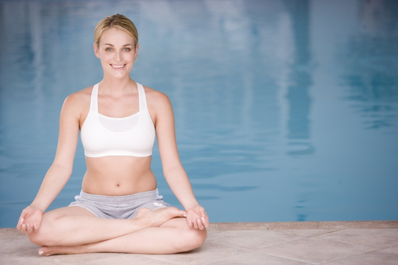 2136886-woman-sitting-poolside-doing-yoga-smiling